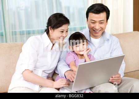 Junges Paar und Tochter schauen Laptop auf sofa - Stockfoto