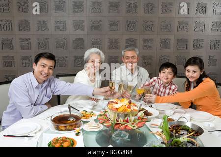 Eltern und Großeltern mit Sohn Toasten am Esstisch - Stockfoto