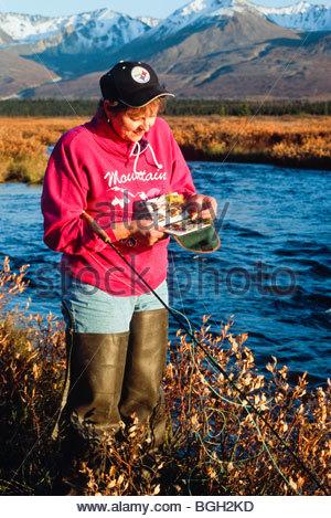 Alaska. Denali Highway. Dame im roten Fischen für Greying. - Stockfoto