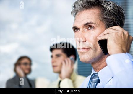 Ein reifer Geschäftsmann und sein Team sprechen auf dem Handy außerhalb - Stockfoto