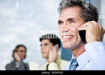 Geschäftsmann und sein Team auf dem Handy - Stockfoto