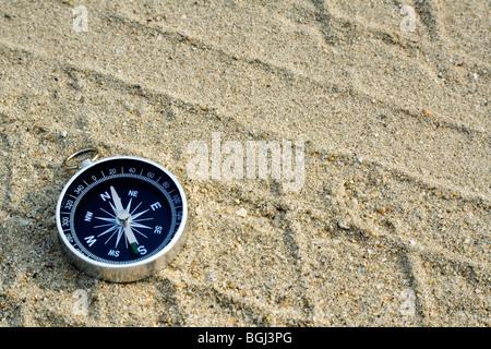 Nahaufnahme eines Kompasses Verlegung auf einem Sandweg - Stockfoto