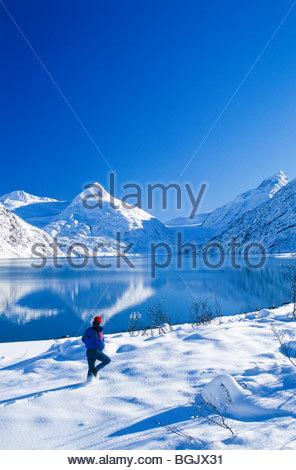 Alaska. Portage Lake. Chugach National Forest. Portage Lake Eisberg und Mann Wandern im Winter. - Stockfoto