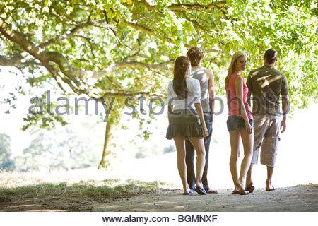 Vier Freunde, die zu Fuß über einen Pfad im Sommer - Stockfoto