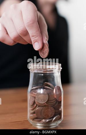 Person fällt eine Münze in Sammlung Glas - Stockfoto