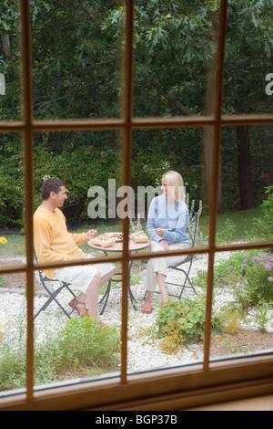 Mitte Erwachsene Frau mit einem reifen Mann zu Mittag in einem Garten - Stockfoto