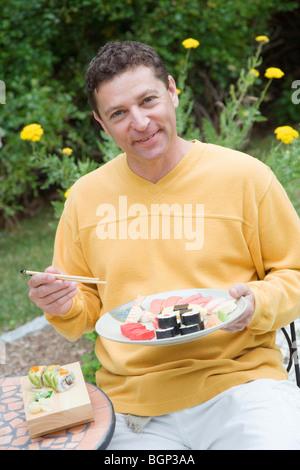 Porträt von einem reifen Mann Essen sushi - Stockfoto