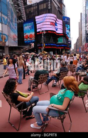 Touristen machen Sie eine Pause vom Sightseeing in den Liegestühlen, die jetzt in der gesamten Times Square vorhanden - Stockfoto