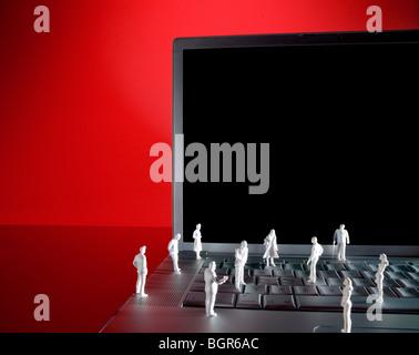 Miniaturfiguren von Menschen stehen auf Tastatur Silber Laptop. Clipping-Pfad enthalten, um Bild in leeren Bildschirm - Stockfoto