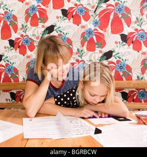 Frau, Mädchen helfen bei den Hausaufgaben, Schweden. - Stockfoto
