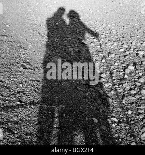 Schatten eines Paares an einem steinigen Strand - Stockfoto