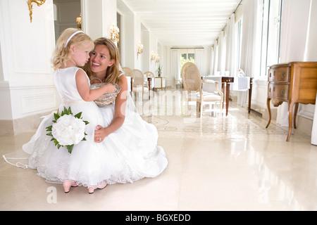 Braut mit jungen Mädchen mit Blumen sprechen - Stockfoto