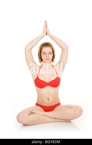 Kaukasische Teenager praktizieren Yoga in einem roten Bikini auf weißem Hintergrund - Stockfoto