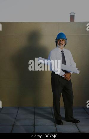 Architekt Entwurf unter Arm, in voller Länge Portrait tragen - Stockfoto