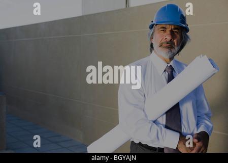 Architekt mit Bauplan unter Arm, Porträt - Stockfoto