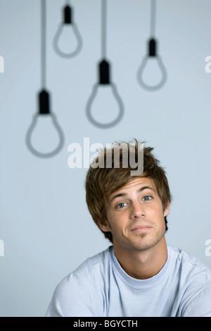 Junger Mann lächelnd in die Kamera, Augenbrauen angehoben - Stockfoto