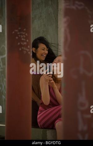 Zwei junge Freundinnen zusammen mit Blick auf Handy, lachen - Stockfoto