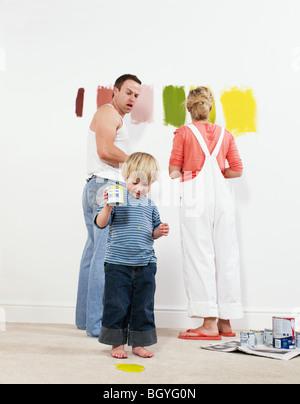 Kleinkind Jungen Gießen Farbe auf Teppich - Stockfoto