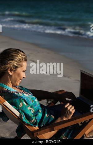 Frau mit Laptop-Computer am Strand - Stockfoto