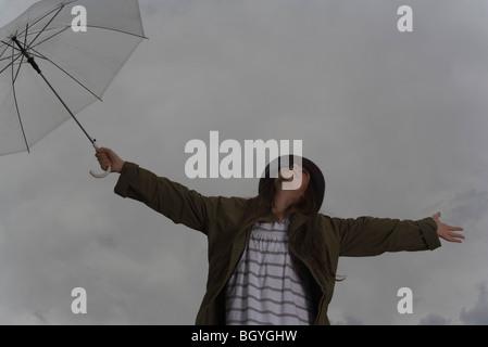 Frau hält Regenschirm mit Armen ausgestreckten und Kopf zurück, blickte in den Himmel - Stockfoto