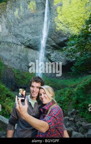 Paar unter Bild vor Wasserfall - Stockfoto