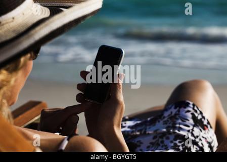 Frau von SMS-Nachrichten mit Smartphone am Strand - Stockfoto