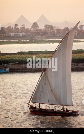 Eine Ladung Typ Feluke Segeln auf dem Nil bei Kairo. Pyramiden sind im Hintergrund zu sehen. - Stockfoto