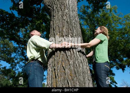 Paar zu halten Hände um Großbaum, Assiniboine Park, Winnipeg, Manitoba, Kanada - Stockfoto