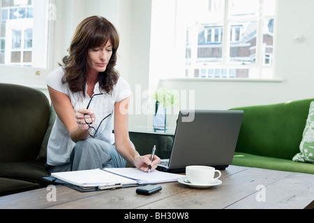 Business-Frauen betrachten Papiere auf sofa - Stockfoto