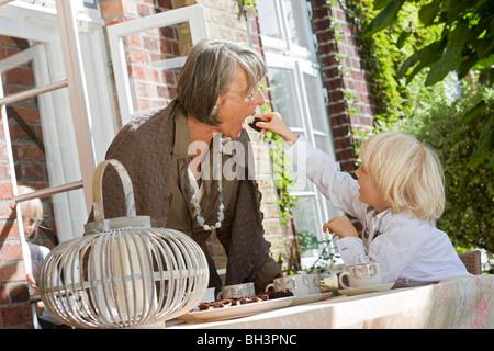 Enkel Fütterung Oma mit Kuchen - Stockfoto