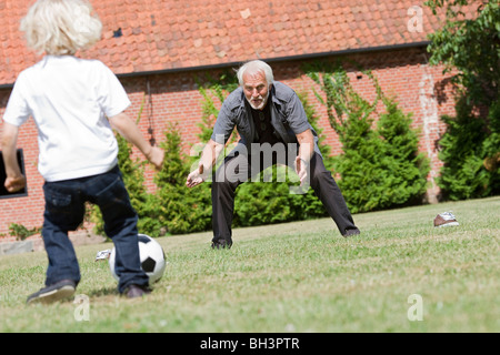 Großvater und Kind Fußball spielen - Stockfoto