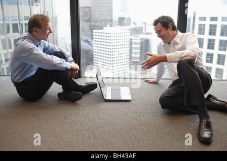 Zwei Geschäftsleute sitzen auf der Büroetage mit einem Laptop-Computer, eine Diskussion, Lächeln - Stockfoto
