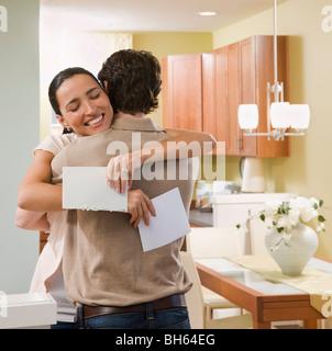 paar, umarmen, nach Erhalt einer Karte - Stockfoto