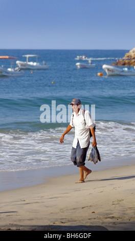 Escondido Oaxaca Mexico, Strand mit lokalen Mann zu Fuß mit Fisch - Stockfoto
