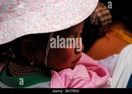 Ecuador, Otavalo, Babymädchen mit einem rosa Hut und goldenen Perlenkette von ihrer Mutter auf dem Rücken getragen - Stockfoto