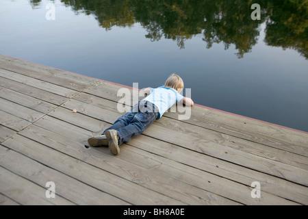 Ein Junge aus einem hölzernen Steg ins Wasser - Stockfoto