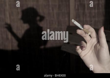 Schatten der jungen Frau Rauchen Zigarette - Stockfoto