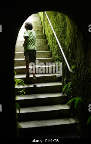 Junge läuft Stufen am Ende des Garten-tunnel - Stockfoto