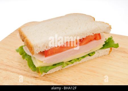 Die Hälfte der Türkei und Käse Sandwich auf weißem Brot mit Salat und Tomate auf einem Schneidebrett auf weißem - Stockfoto