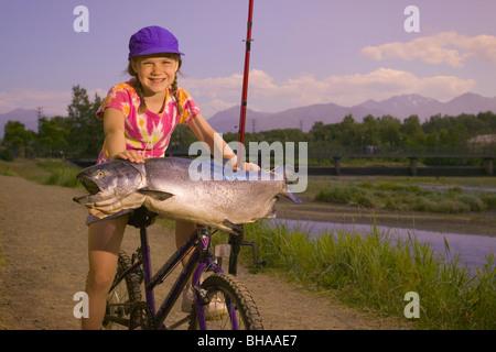 Junges Mädchen auf Fahrrad hält King Salmon Digital SC AK Sommer Ship Creek - Stockfoto