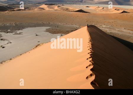 Wandern entlang der unberührten Grat einer riesigen roten Sanddüne in der Wüste von Namibia - Stockfoto