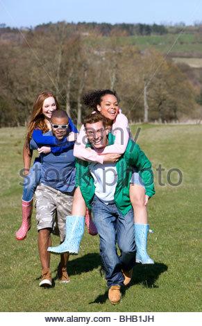Paare im Feld Huckepack - Stockfoto