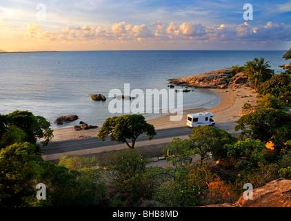 Touristen in einem Reisemobil entlang Bowen's Horseshoe Bay bei Sonnenuntergang fahren, während der Tour in Queensland - Stockfoto