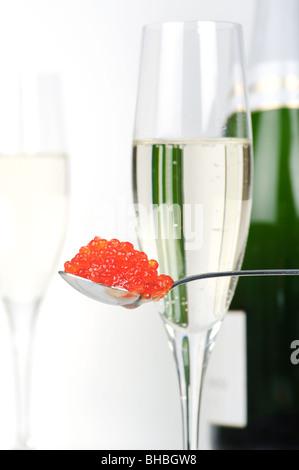 Ein Löffel mit Lachs Kaviar vor voller Champagner-Gläser und eine Flasche Champagner. Fokus auf Kaviar. - Stockfoto