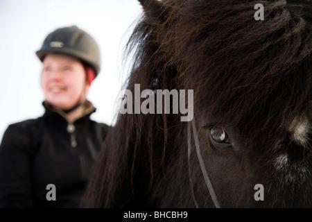 Auf dem Pferderücken lächelnde Frau. Skagafjördur Island - Stockfoto