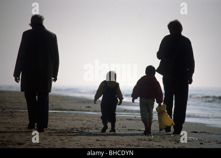 1970er Jahre: Familie spaziergang Sonnenuntergang am Strand. - Stockfoto