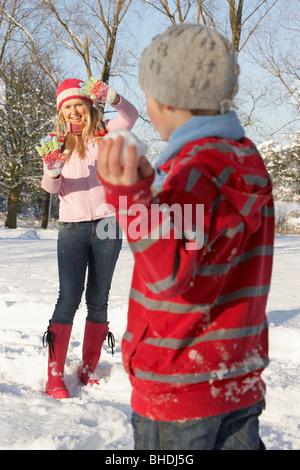 Mutter und Sohn mit Schneeballschlacht In Schneelandschaft - Stockfoto