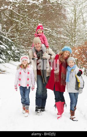 Familie zu Fuß durch den verschneiten Wald - Stockfoto
