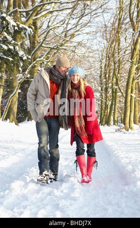 Paare, die durch den verschneiten Wald - Stockfoto
