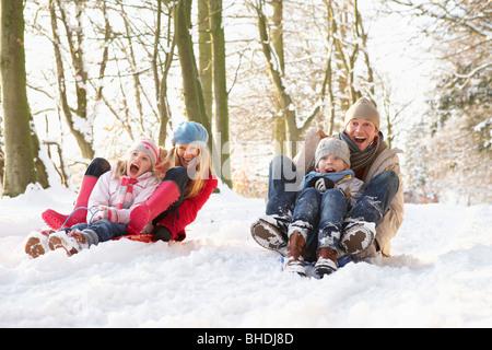 Familie Schlittenfahrten durch den verschneiten Wald - Stockfoto